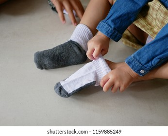 Little baby girl's hands putting on socks by herself -  children development by learning to do things by themselves