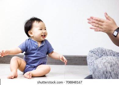 A little baby is happy playing with his mother while mother is clapping her hands. Baby is sitting on the floor. White and grey background.