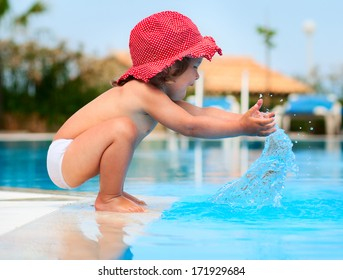 Little baby have a fun with a splash near swimming pool