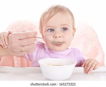 Little baby having fun eating children's porridge