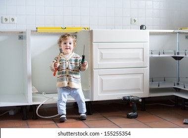 Little baby helping to assemble a kitchen in a new home