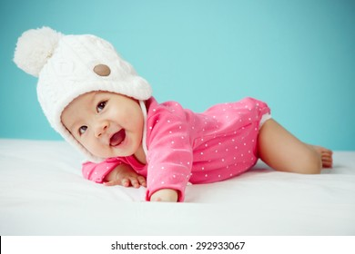 Little baby in knit winter clothing closing face with knitted beanie on the bed in the blue bedroom, New family and baby protection concept