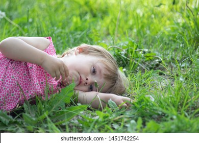 Little baby is laying on the evening glade and crying.