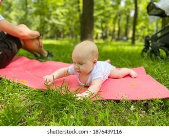 Ein kleines Baby liegt auf dem Gras und reißt es auf. Sein Vater kümmert sich um ihn. Erkunden Sie die Welt.