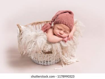 Little baby in light pink-red knitted beanie sweetly sleeping on the white coverlet in the basket on the light background