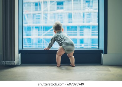A little baby is looking out the window of a high rise apartment