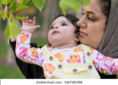 Little baby is looking and touching new spring leaves in her mother's hug, outdoor area.