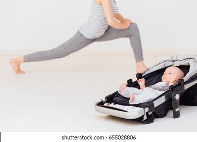 Little baby lying in child pram while his mother workout on the background. Focus on baby boy. Fitness maternity healthy lifestyle concept.