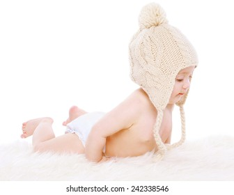 Little baby lying in knitted hat on a white background