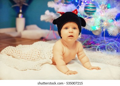Little baby lying near the tree. The concept of Christmas