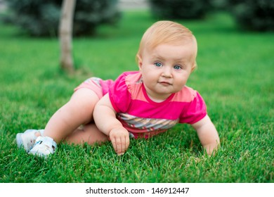 little baby lying on the grass in the park