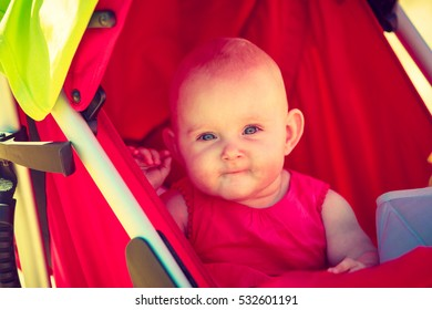 Little baby lying in pram with dummy in mouth on sunny day