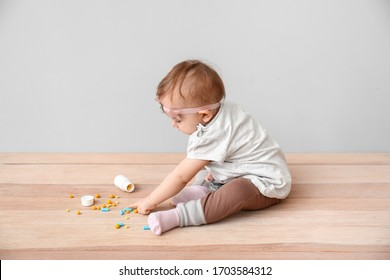 Little baby with medicines on grey background. Child in danger