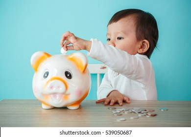 Little baby moneybox putting a coin into a piggy bank, kid saving money for future concept