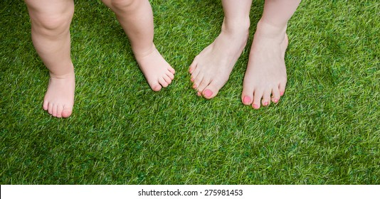 Little baby and mother legs standing  on grass