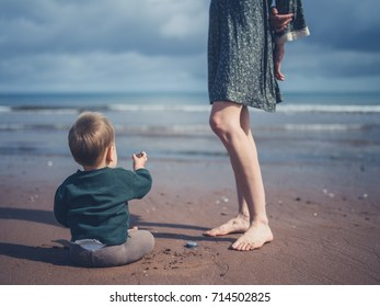 A little baby is on the beach playing by the feet of his mother