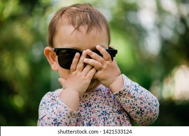 Little baby playing bo-peep girl hiding face. Summer background. Sunglasses