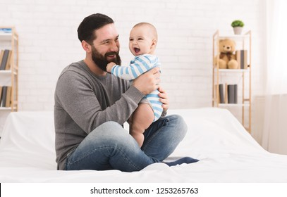 Little baby playing with daddy beard and laughing, copy space