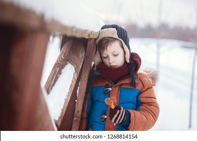 Little Baby playing and eating sweet cockerel in winter day. Kids play in snowy forest
