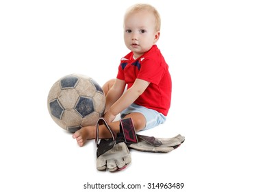 Little baby is playing with a football. He is very happy.