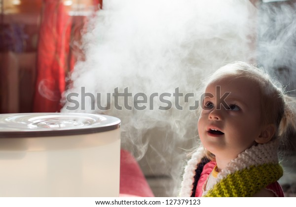 Little baby playing with humidifier