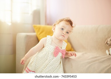 Little baby playing on at home. A small baby girl is left alone in her room
