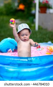 Little baby playing with rubber toys in inflatable pool in the summer sunny day/Young toddler boy playing in kiddie pool with rubber ball