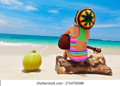 Little baby in rasta hat play reggae music on Hawaiian ukulele, enjoy relaxing on ocean beach. Kids healthy lifestyle. Family summer holiday. Activity on tropical Jamaica and Caribbean island travel.