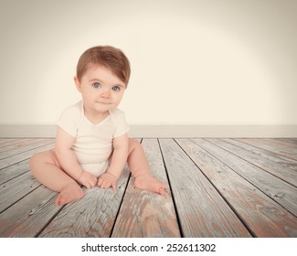 A little baby is sitting on a wooden floor with a blank white wall in the background and looks happy with copyspace for a message.