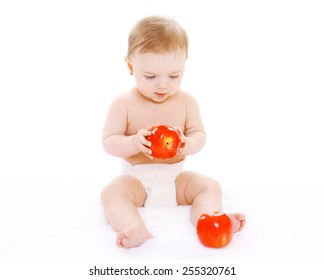 Little baby sitting with reds apples on a white background