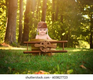 A little baby is sitting in a wooden airplane basket prop in the park pretending to travel and fly with a pilot hat on for a creativity or imagination concept.