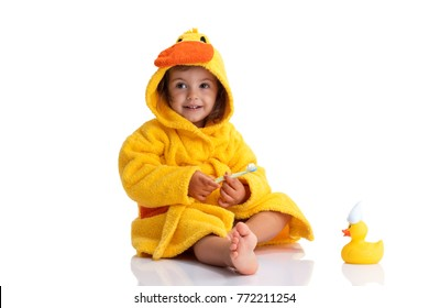 Little baby smiling under a yellow towel and brushing his teeth.