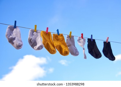 Little baby socks dry on the street against a blue sky