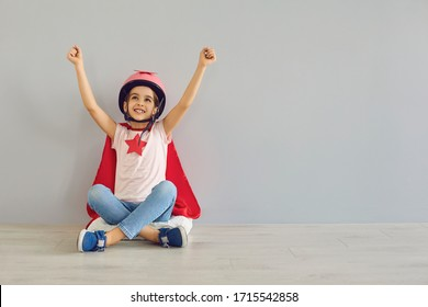 Little baby superhero in a helmet smiles raised his hands while sitting on floor against a gray background.