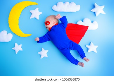 Little baby superhero with red cape flies through the night sky.Children in thematic costumes.