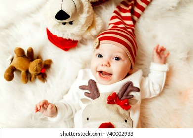 Little baby in sweater with a deer and red hat lies on soft white blanket