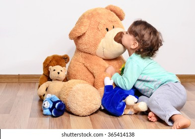 Little baby toddler playing with his teddy bears. Cute boy loving and kissing his big teddy bear toy.