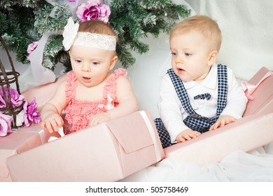 Little baby twins boy and girl with christmas tree and gift