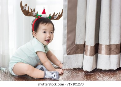 A little baby is wearing Christmas reindeer antlers while sitting on the floor. Baby is happy to celebrate Christmas and New Year. Grey background.