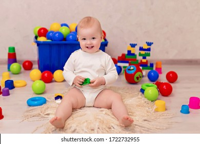 little baby in white clothes sits and plays with a multi-colored designer at home, child development