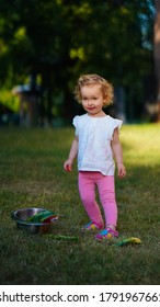Little baby in white shirt and pink tights with pan and scattered watermelon stubs in park