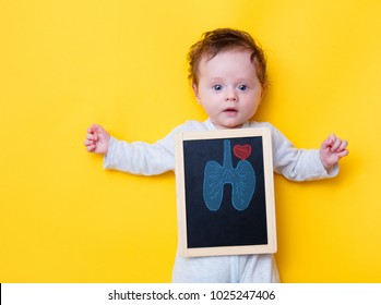 little baby with X-ray board and drawing lungs and heart on yellow background