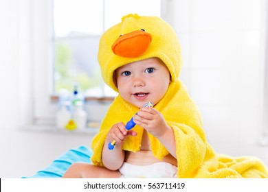 Little baby in yellow duck towel brushing teeth on changing table after bath. Infant boy with tooth brush. Dental hygiene, toothbrush and toothpaste for young kids. Child teeth and oral health care