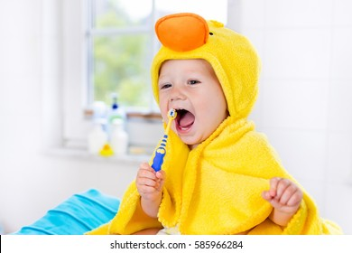 Little baby in yellow duck towel brushing teeth on changing table after bath. Infant boy with tooth brush. Dental hygiene, toothbrush and toothpaste for young kids. Child teeth and oral health care.