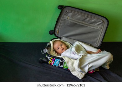 little babyboy lying in the suitcase covered in blanket on black ground with green background