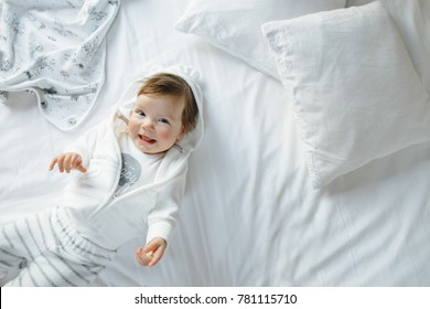 Little baby-girl dressed in casual-style lies on white bed