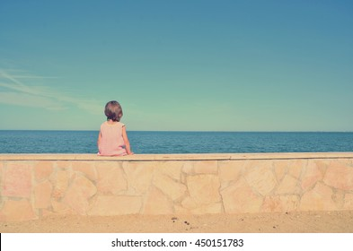 Little baby-girl sitting alone against the sea. Retro effect.
