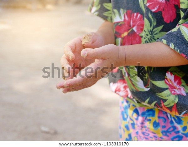 Little baby's hands getting dirty with sand from the beach - Let children get dirty sometimes, as it's essential for their physical and mental development