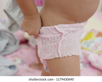 Little baby's hands pulling a diaper up / putting it on by herself - child development by allowing them to do things by themselves