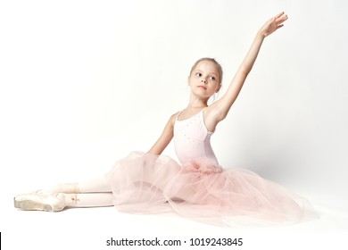 little ballerina in a beautiful suit dancing ballet on a light background